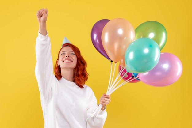 Widok z przodu młodej kobiety trzymającej śliczne kolorowe balony na żółtej ścianie