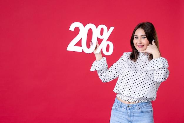 Widok z przodu młodej kobiety trzymającej zniżkę i uśmiechającej się na czerwonej ścianie