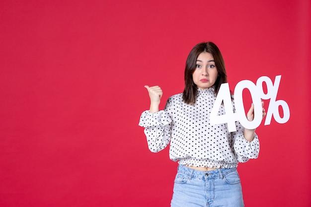 Widok z przodu młodej kobiety trzymającej zniżkę na czerwonej ścianie