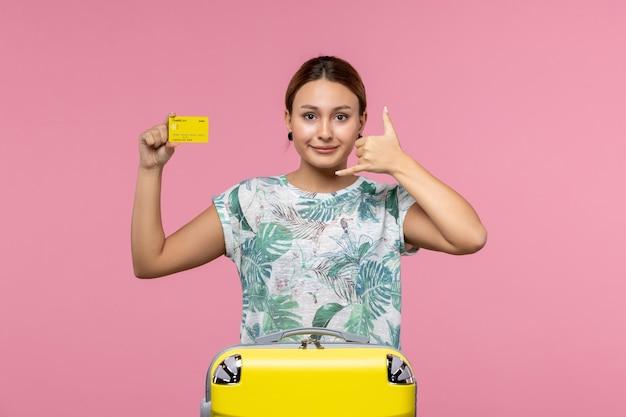 Widok z przodu młodej kobiety trzymającej żółtą kartę bankową na jasnoróżowej ścianie