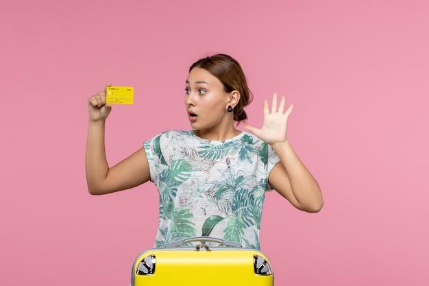 Widok z przodu młodej kobiety trzymającej żółtą kartę bankową na różowej ścianie
