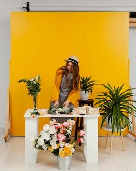 Widok z przodu młodej kobiety układania kwiatów