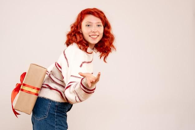 Widok z przodu młodej kobiety ukrywa prezent gwiazdkowy za plecami na białej ścianie