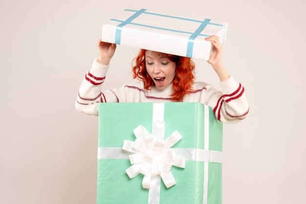 Widok z przodu młodej kobiety ukrywającej się wewnątrz prezentu bożonarodzeniowego na białej ścianie