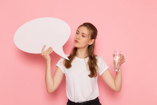 Widok z przodu młodej kobiety w białej koszulce trzymającej biały znak i szklankę wody na różowej ścianie