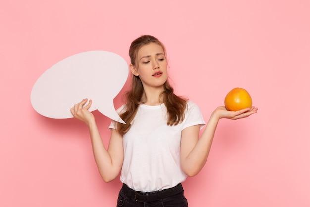 Widok z przodu młodej kobiety w białej koszulce trzymającej grejpfruta i biały znak na różowej ścianie