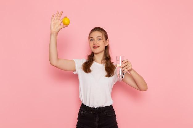 Widok z przodu młodej kobiety w białej koszulce trzymającej świeżą cytrynę i szklankę wody na jasnoróżowej ścianie