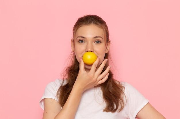 Widok z przodu młodej kobiety w białej koszulce trzymającej świeżą cytrynę uśmiechniętej na różowej ścianie