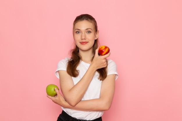 Widok z przodu młodej kobiety w białej koszulce trzymającej świeże zielone jabłko z brzoskwinią uśmiechniętej na jasnoróżowej ścianie