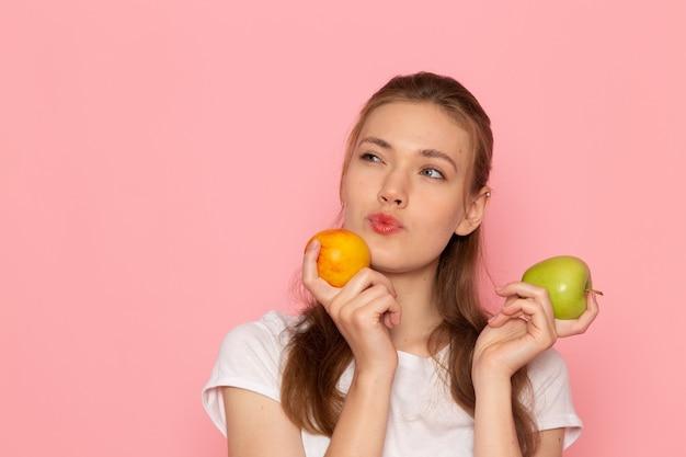 Widok z przodu młodej kobiety w białej koszulce trzymającej świeże zielone jabłko z brzoskwiniowym myśleniem na jasnoróżowej ścianie