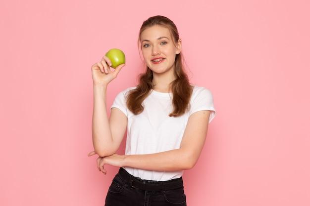 Widok z przodu młodej kobiety w białej koszulce trzymającej zielone jabłko i uśmiechającej się na różowej ścianie