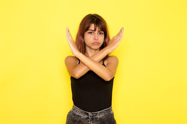 Widok z przodu młodej kobiety w czarnej koszuli i szarych dżinsach przedstawiających znak zakazu na żółtej ścianie