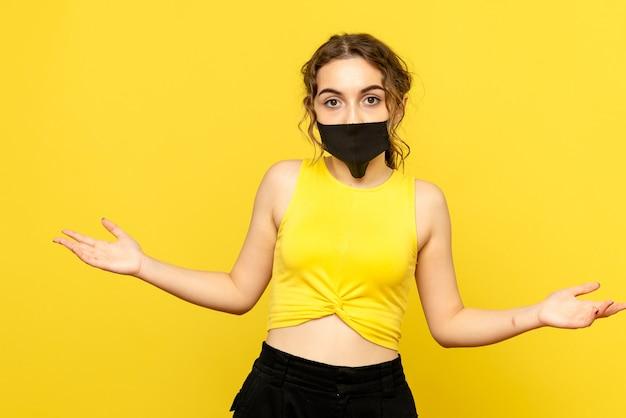 Widok z przodu młodej kobiety w czarnej masce na żółtej ścianie