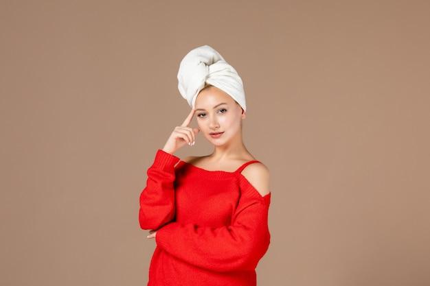 Widok z przodu młodej kobiety w czerwonej koszuli z ręcznikiem na głowie brązowa ściana
