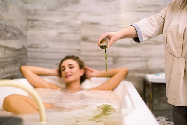 Widok z przodu młodej kobiety w kąpieli podczas hydromasażu w salonie piękności. terapeuta wypełnia wannę specjalnym składnikiem do hydromasażu.