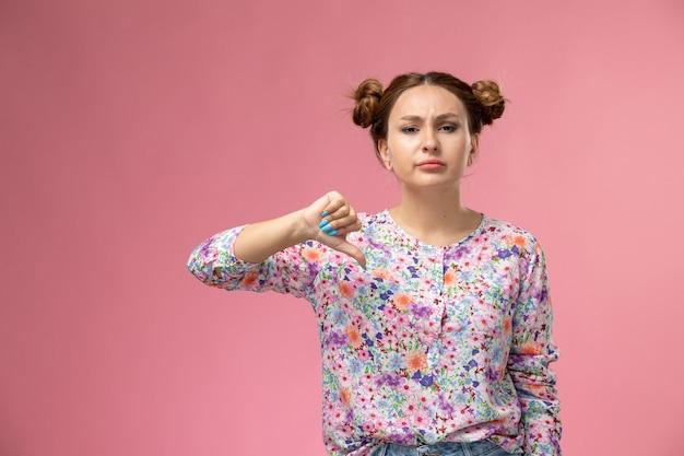 Widok z przodu młodej kobiety w koszuli w kwiaty i niebieskich dżinsach przedstawiających inny znak na różowym tle