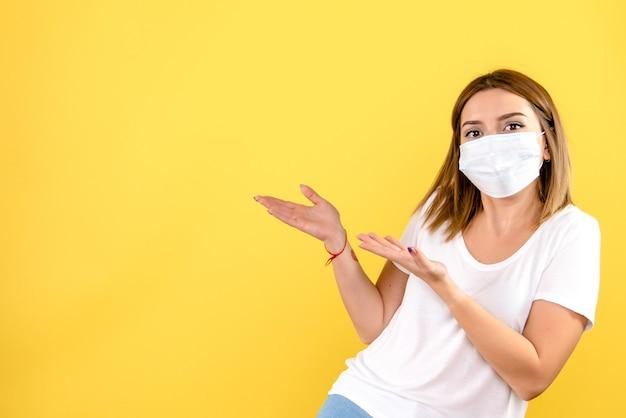Widok z przodu młodej kobiety w masce na żółtej ścianie