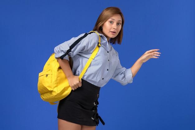 Widok z przodu młodej kobiety w niebieskiej koszuli, czarnej spódnicy, ubrana w żółty plecak, pozowanie i biega po jasnoniebieskiej ścianie