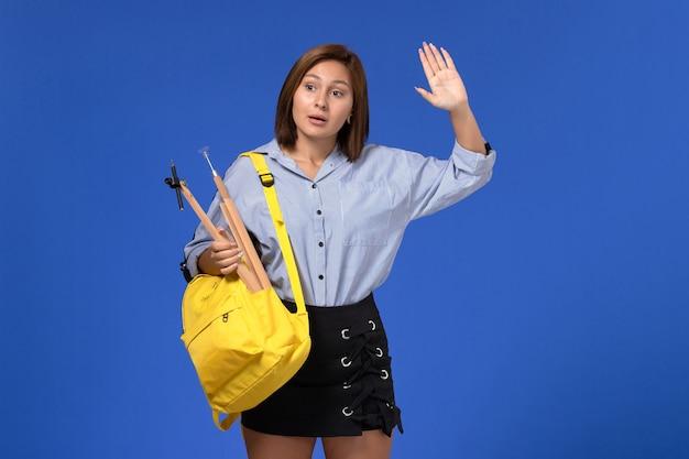 Widok z przodu młodej kobiety w niebieskiej koszuli w żółtym plecaku trzymającej drewnianą figurę na jasnoniebieskiej ścianie