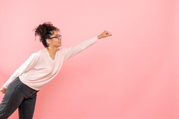 Widok z przodu młodej kobiety w pozie supermana na różowej ścianie