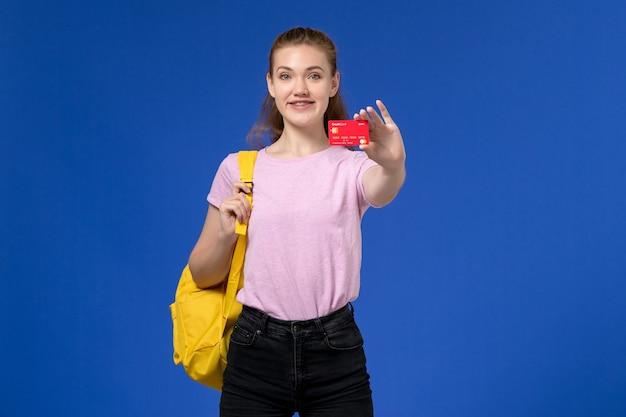 Widok z przodu młodej kobiety w różowej koszulce na sobie żółty plecak, trzymając plastikową czerwoną kartkę na niebieskiej ścianie