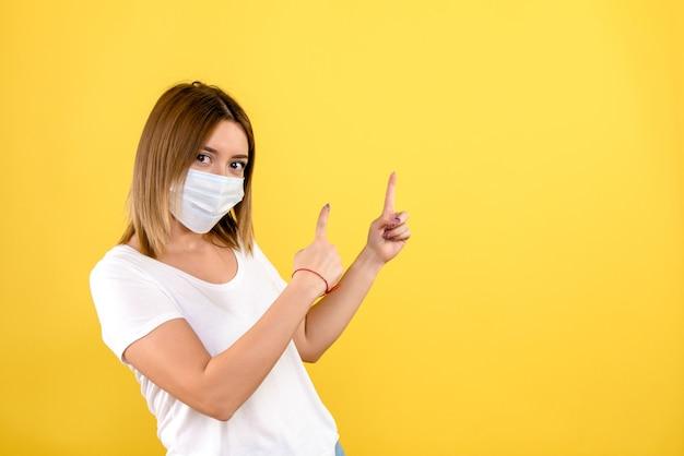 Widok z przodu młodej kobiety w sterylnej masce na żółtej ścianie
