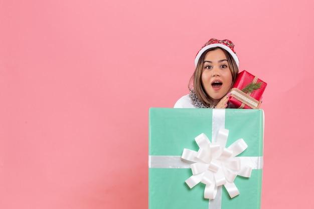 Widok z przodu młodej kobiety wewnątrz prezentu trzymającego inny prezent na różowej ścianie