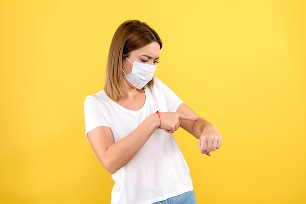 Widok z przodu młodej kobiety, wskazując na jej nadgarstek na żółtej ścianie