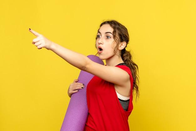 Widok z przodu młodej kobiety, wskazując na odległość na żółtej ścianie