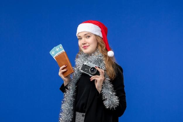 Widok z przodu młodej kobiety z biletami i aparatem na niebieskiej ścianie