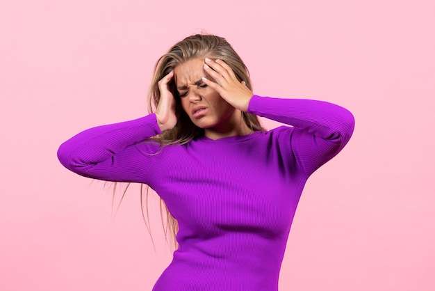 Widok z przodu młodej kobiety z bólem głowy w pięknej fioletowej sukience na różowej ścianie