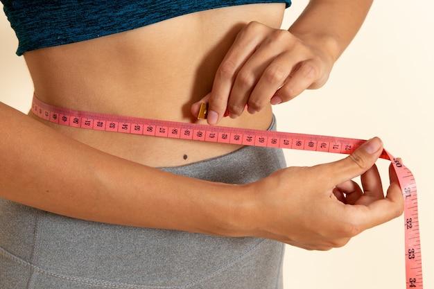 Widok z przodu młodej kobiety z dopasowanym ciałem w koszuli mierzącej jej talię na białej ścianie