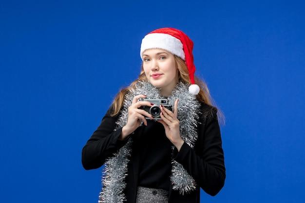 Widok z przodu młodej kobiety z kamerą na niebieskiej ścianie