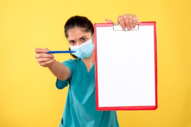 Widok z przodu młodej kobiety z maską medyczną trzymając schowek na żółtej ścianie