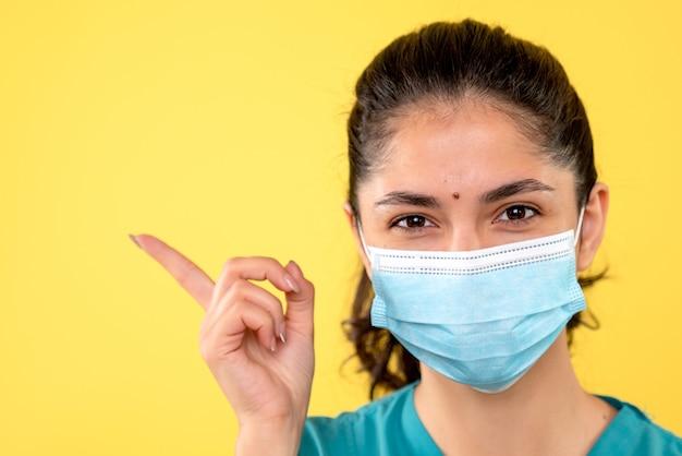 Widok z przodu młodej kobiety z maską medyczną, wskazując palcem coś na żółtej ścianie