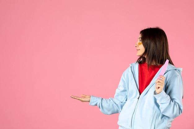 Widok z przodu młodej kobiety z opaskami na oczy i pilnikiem do paznokci na różowej ścianie