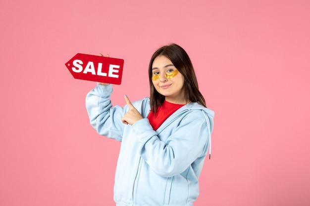 Widok z przodu młodej kobiety z opaskami na oczy trzymający transparent sprzedaży na różowej ścianie
