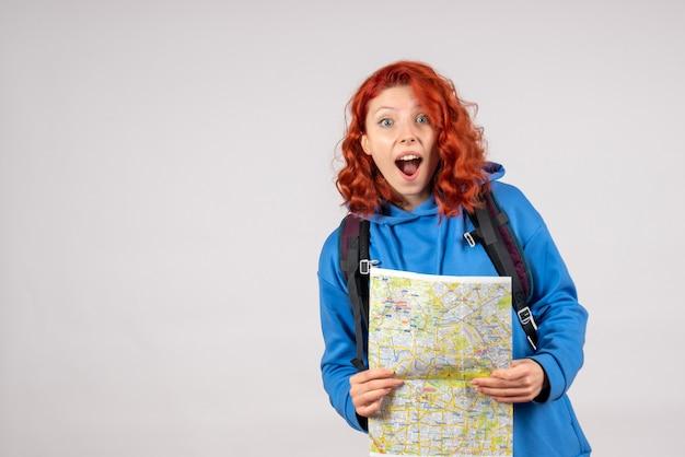 Widok z przodu młodej kobiety z plecakiem i mapą na białej ścianie
