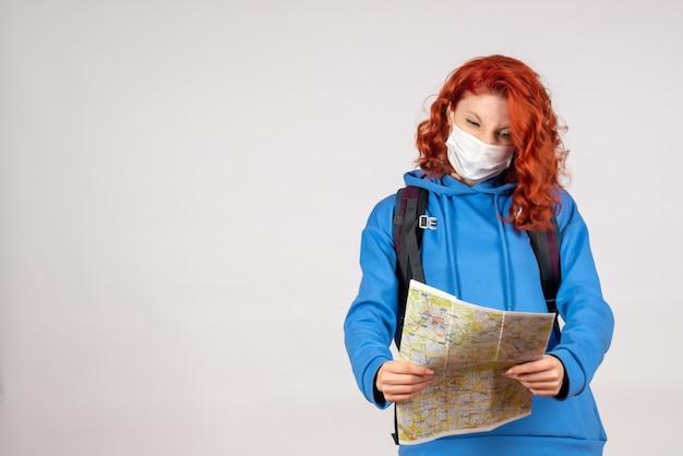 Widok z przodu młodej kobiety z plecakiem i mapą w masce na białej ścianie