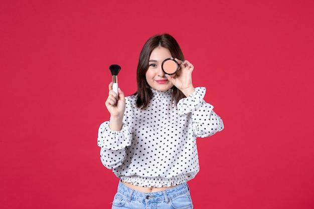 Widok z przodu młodej kobiety z pomponem i proszkiem robi makijaż na czerwonej ścianie