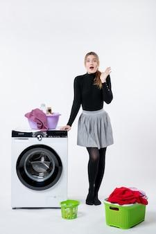 Widok z przodu młodej kobiety z pralką i brudnymi ubraniami na białej ścianie
