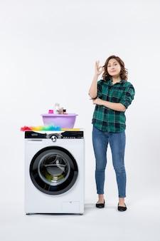 Widok z przodu młodej kobiety z pralką na białej ścianie
