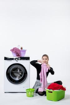 Widok z przodu młodej kobiety z pralką składającą brudne ubrania na białej ścianie