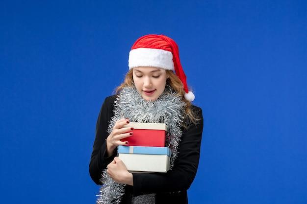 Widok z przodu młodej kobiety z prezentami noworocznymi na niebieskiej ścianie