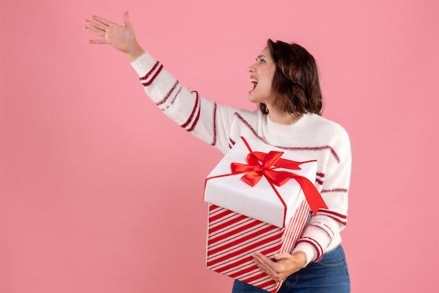 Widok z przodu młodej kobiety z prezentem na różowej ścianie