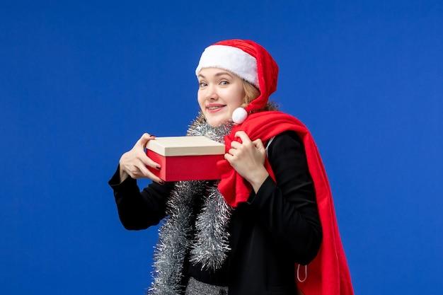 Widok z przodu młodej kobiety z prezentem świątecznym na niebieskiej ścianie