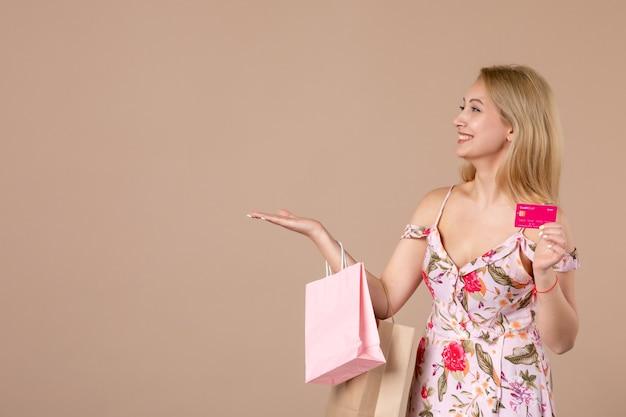 Widok z przodu młodej kobiety z torbami na zakupy i kartą bankową na brązowej ścianie