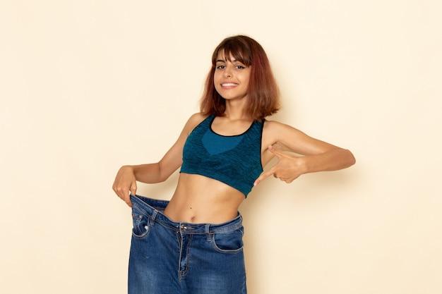 Widok z przodu młodej kobiety z wysportowanym ciałem w niebieskiej koszuli sprawdzającej swoją wagę na jasnobiałej ścianie