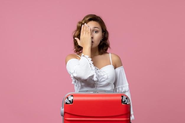 Widok z przodu młodej kobiety zakrywającej połowę twarzy czerwoną torbą na różowej ścianie