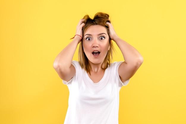 Widok z przodu młodej kobiety zaskoczony na żółtej ścianie